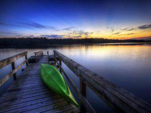 Canoa verde en el muelle del lago