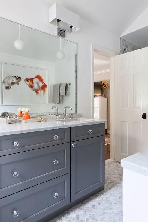 Marble herringbone floor tiles frame a gray washstand accented with glass knobs and a white marble countertop fitted with a rectangular undermount sink and a polished nickel faucet fixed beneath a frameless vanity mirror reflecting a framed fish art piece.