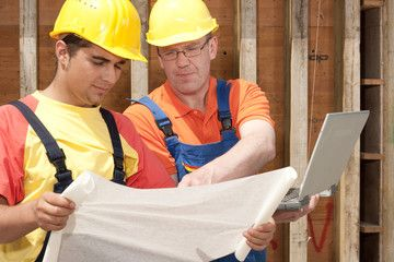 two workers with a notebook on a construction site