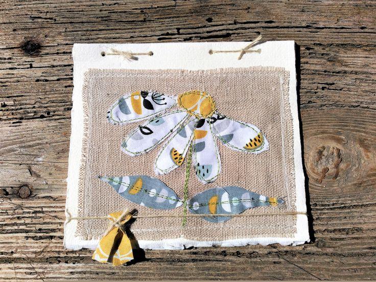 Postal de paper fet a mà i aplicacions de roba de cotó i lli.