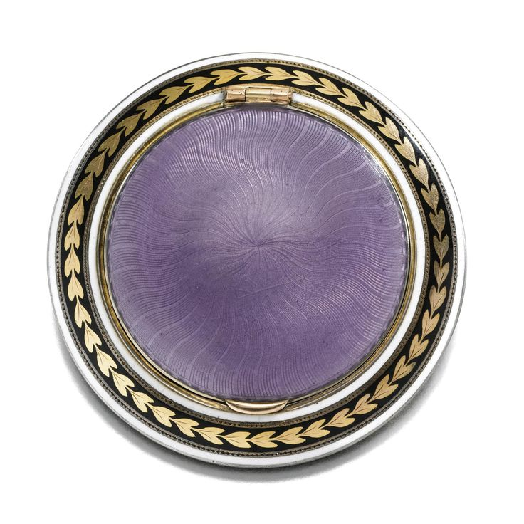 A Fabergé silver-gilt and enamel compact, workmaster Henrik Wigström, St Petersburg, 1908-1917, shallow circular form, the lid and base enamelled in translucent lavender over wavy sunburst engine-turning, the borders of gilt laurel on a black ground. PROVENANCE: This was formerly in the collections of descendants of Henrik Wigström, having been passed down through three generations of the family from Wigström's daughters, Lyyli and Hellin.