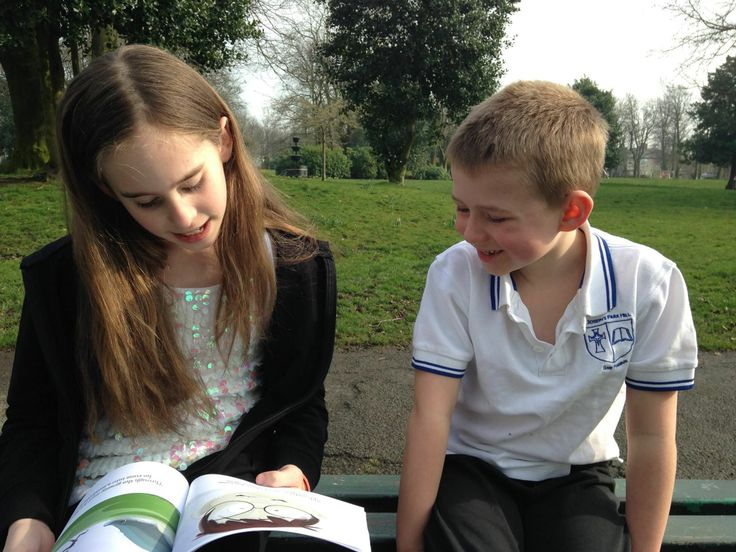 Some young readers enjoying our book in the park.