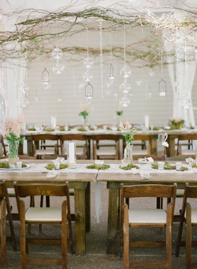 Love the grapevine branches above with glass globes hanging down. Moss centerpieces.