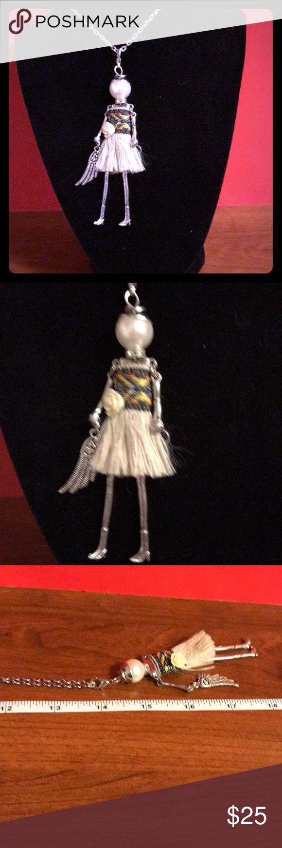 UNIQUE IZZY DOLL NECKLACE Our unique Izzy doll necklace is on a silver 13 inch chain, silver legs and arms silver angel wing.Pearlized face, beige skirt and flowe. Wonderful for yourself or a wonderful present for a loved one. IZZY is our Favorite doll necklace..She is brand new. Lucy & Ethel Jewelry Necklaces