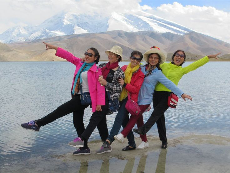 Chinese tourists pose before Lake Karakol on the Pamir Plateau with Muztagh Ata (7,509 meters) in the background.