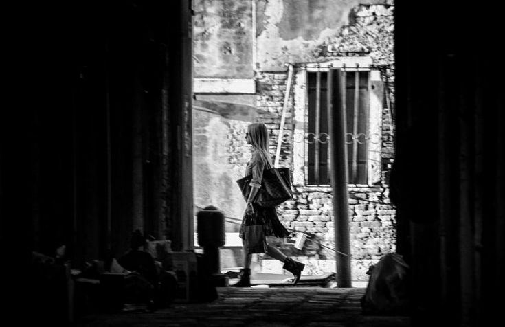 Due gondolieri che aspettano il prossimo cliente, un prete che attraversa il colonnato e un uomo che passeggia lungo un canale della laguna. Queste immagini sono una dedica tutta particolare rivolta a Venezia: il fotografo  Ando Fuchs  ha voluto immortalare una città solitaria e silenziosa, l