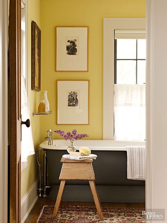 Deep window trim, tall baseboards, and weathered wood flooring pay witness to this home's century-past beginnings. Sunny yellow walls highlight a vintage-look pedestal tub and eclectic artwork. A country stool and an antique area rug enhance the bathroom's assembled-over-time appeal./