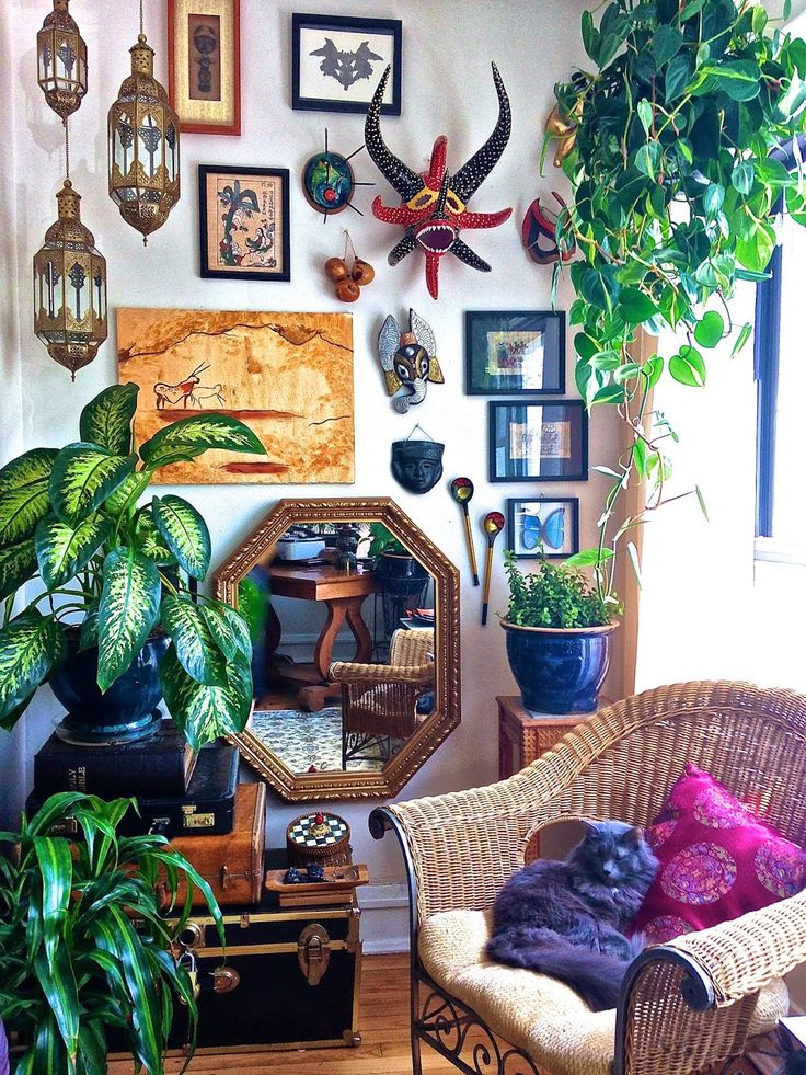 nicely arranged items and art on walls combined with hanging lanterns and plants. ..wicker chair, trunks ..Well done