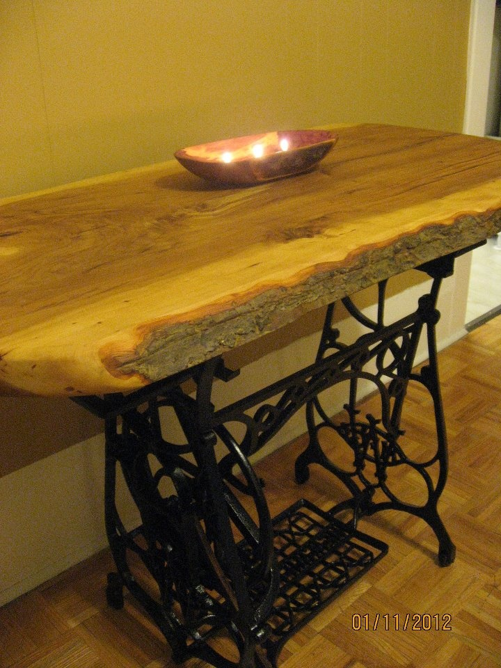 One-of-a-kind table. Apple wood from Toronto Island on top of an antique sewing machine base.