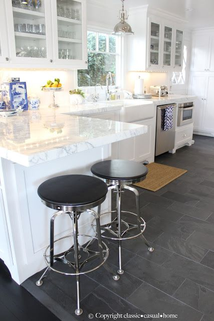 straight edge on the white marble and the slate floor.    The counter stools are from Restoration Hardware.