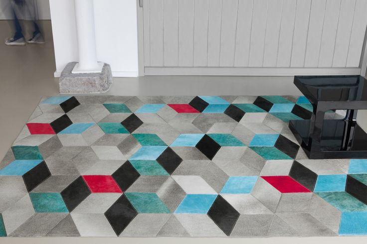CODEN Collection 'Coden' or the simple and elegant interpretation of geometric motifs with a modern feel. Touches of sky blue, bright red and cyan  light up and accentuate the 3D checked effect of this trompe-l'œil. A rug in 100% leather for colourful homes with a designer look.