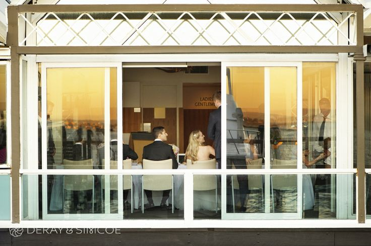 Beautiful, warm sunset light falls over the balcony. Wedding reception styling, ideas and inspiration.  Reception Venue: Mosman's Restaurant  Photography by DeRay & Simcoe
