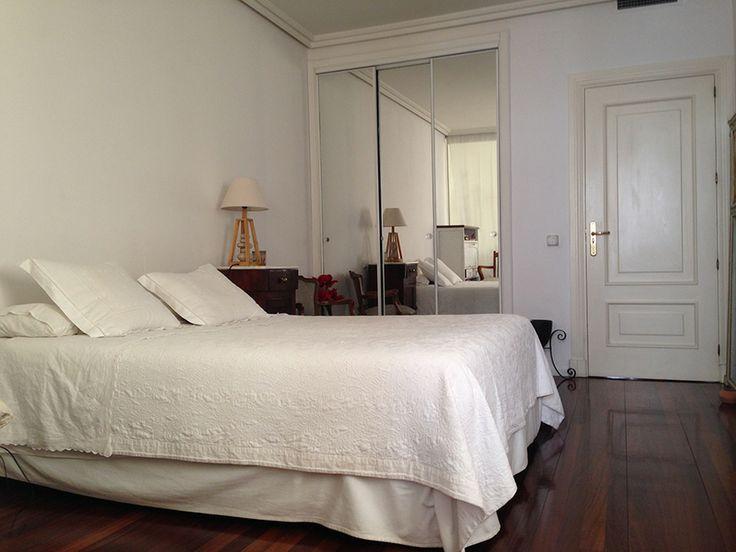 el dormitorio principal de la suite, visto desde el cuarto de baño. Al fondo de la imagen, a la izquierda, las puertas del vestidor, compuesto de seis paneles de armario. Fuera de imagen, en la parte superior de la puerta, se encuentra la rejilla de distribución de aire acondicionado.