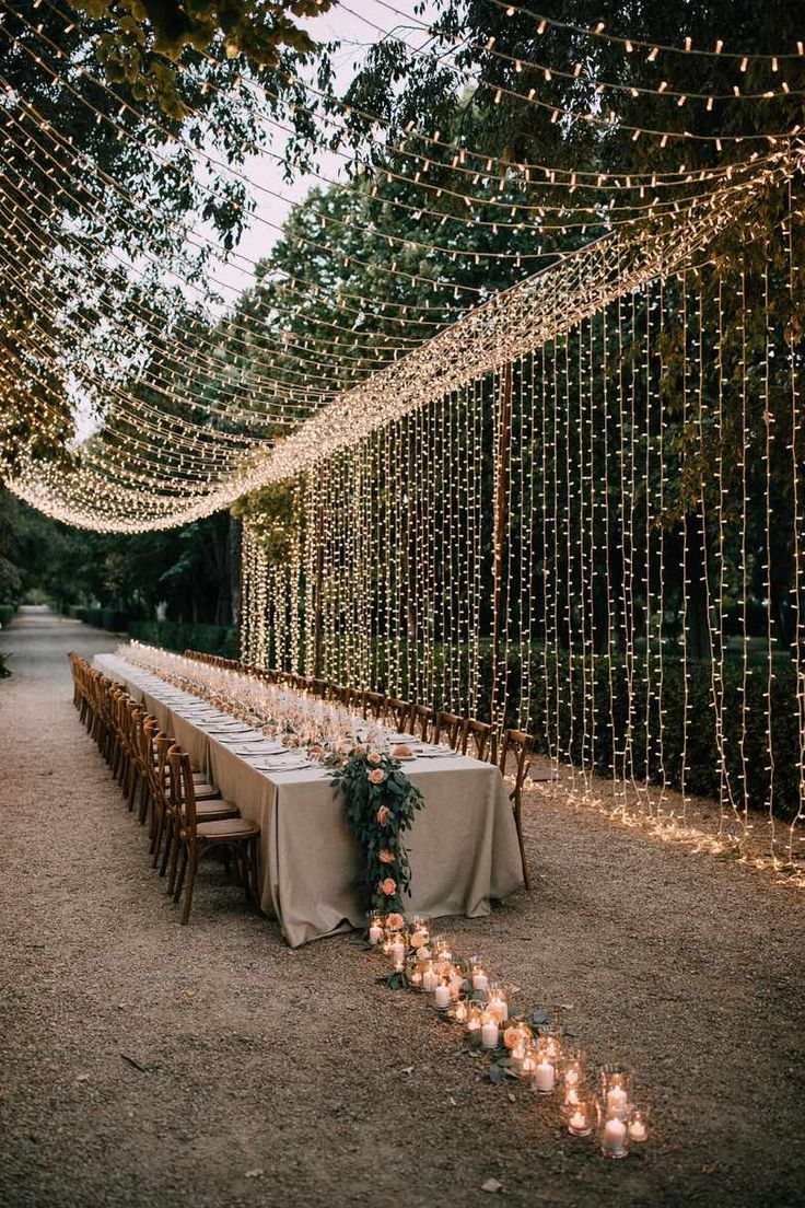 A wedding uses white candles, flowers and string lights as decorations.