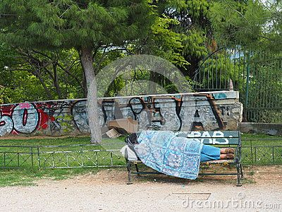 View of  unidentified homeless person sleeping rough on a park bench in Athens, Greece. Homelessness is a growing symptom of the economic recession.