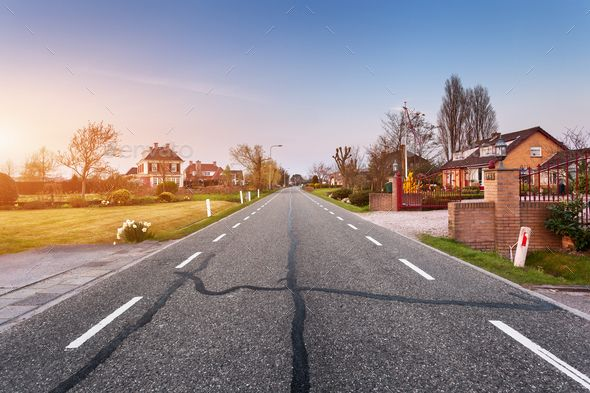 Landscape with asphalt road through the town at sunset by den-belitsky on PhotoDune. Beautiful landscape with european asphalt road through the town with houses and courtyards at sunset in Netherlands. ...