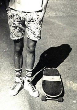 An early skater showing off his style. The bottom half of the skateboarder, who is wearing shorts with graphics, and his skateboard are depicted.