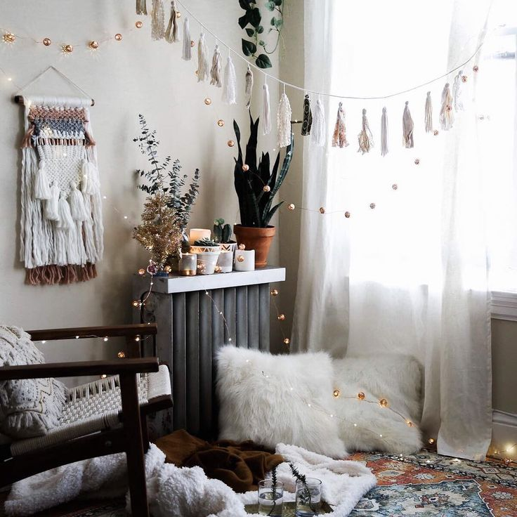 Hygge in a picture. Fluffy cushions, fairy lights, weavings and boho colours. Gorgeous room.