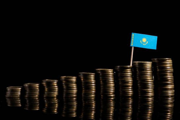 kazakhstan flag with lot of coins isolated on black background