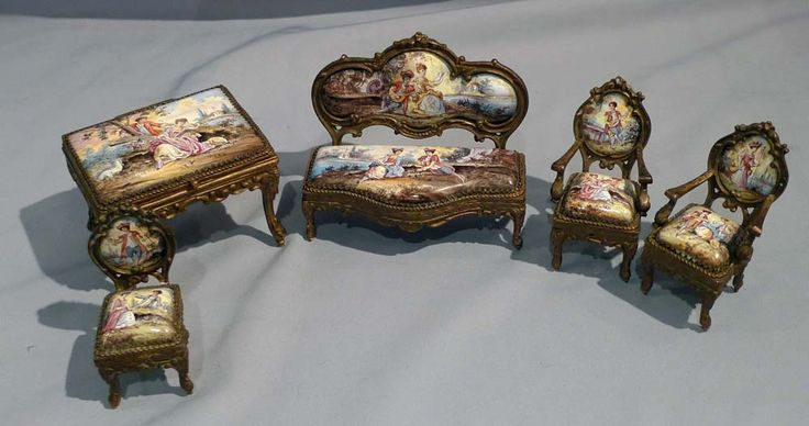 Fine set of miniature austrian hand painted enamel and gilt bronze furniture. Including a table with hinged lid with finely painted top, a sofa, two arm chairs and a dining chair. Austrian circa 1890.