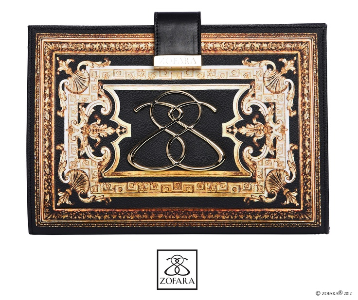 """Introducing the Zofara """"Futurity Crest Clutch"""" Available now. The Futurity Crest Clutch defines evening glamour.  This opulent and decorative piece embellished with  Zofara's rich golden emblem adding to its charm,  encapsulates femininity and enhances any  ensemble. Hold as a clutch or wear across  the body with the detachable gold chain  and black leather shoulder strap."""