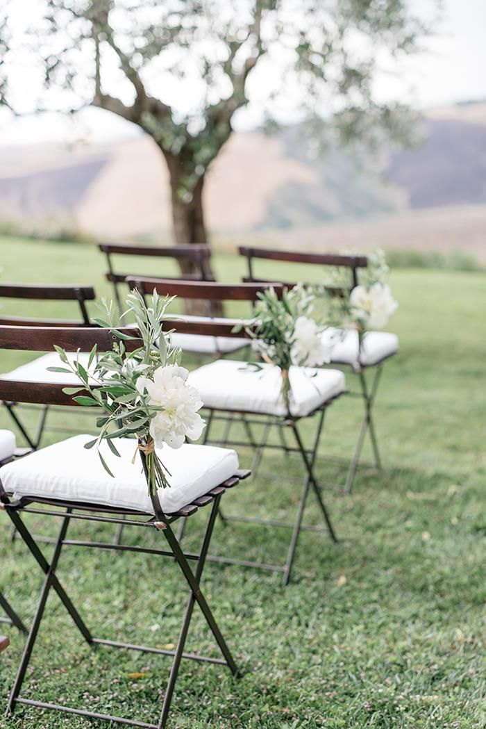 Simple and elegant ceremony aisle markers made of white peonies and olive branches. #wedding #flowers