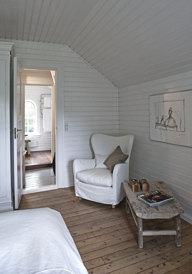 Feminine, delicate reading space in the bedroom with a white armchair and raw wooden table.