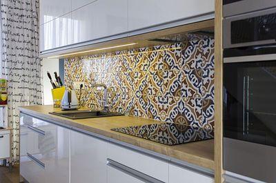 Dvířka kuchyňské linky jsou v bílém lesku, pracovní plocha dřevěná a panel za ní pestrobarevný. Celek je zmenšenou kopií barevné palety použité pro společenský prostor v přízemí.