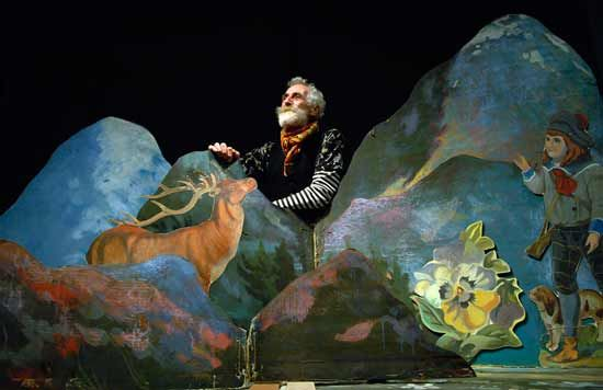 John Byrne behind a 'cut-out' of hills and a stag