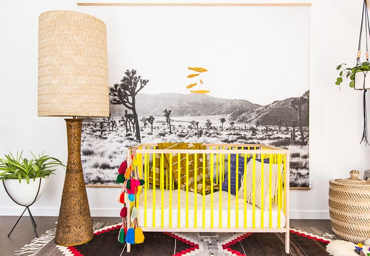 Non-traditional nursery with yellow crib, large floor lamp, and hanging desert graphic on the wall: