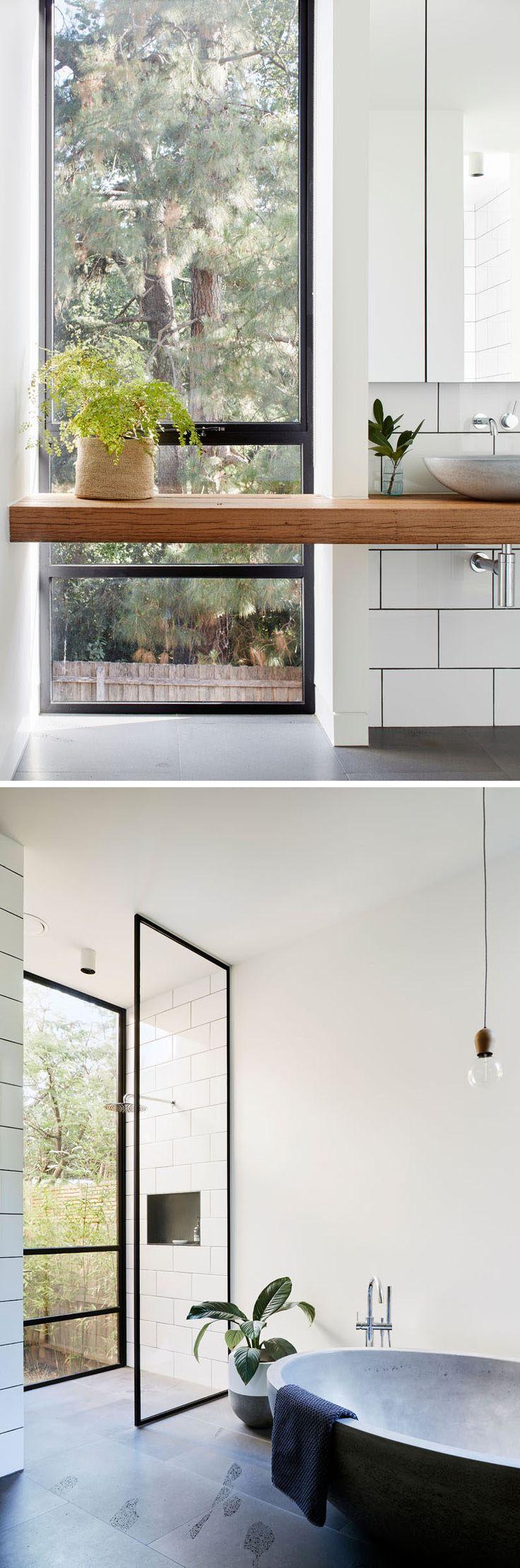 Este banheiro moderno é mantido brilhante e arejado com o uso de divisórias de vidro e paredes e azulejos brancos.  Acentos negros são utilizados em toda a forma de marcos de janelas e argamassa de telha.