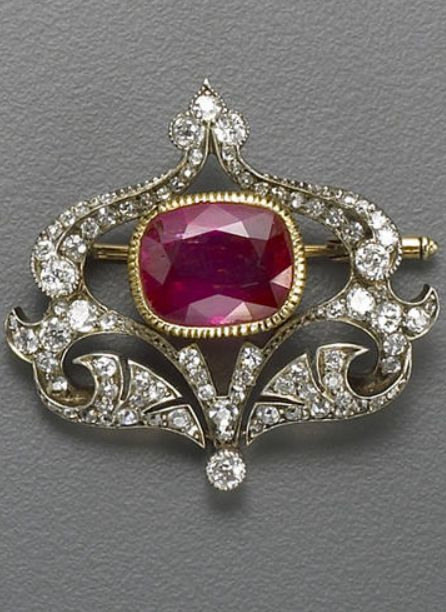 An antique ruby, diamond and silver topped gold brooch, circa 1880 centering a bezel-set cushion-shaped ruby within an openwork shield-shaped panel of old European and single-cut diamonds; ruby weighing an estimated: 8.20 carats.