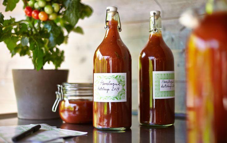 Duas garrafas e um recipiente de molho de tomate caseiro, bem como um tomateiro, sobre uma bancada de cozinha.