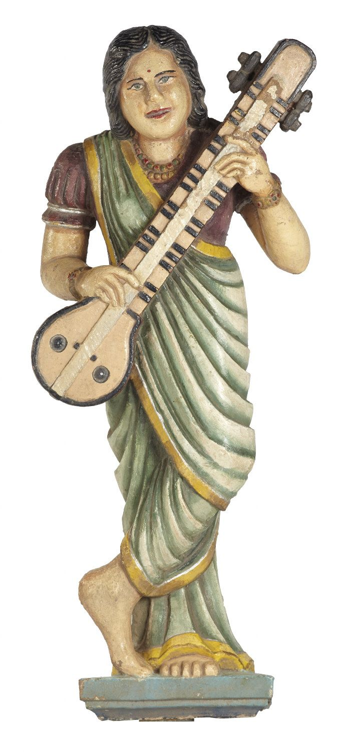 This carved and painted figure represents an apsara, the nymphs who serve as musicians and dancers at the court of Indra, the King of the Gods in Hindu, Buddhist and Jain mythology. Such figurines are often incorporated into the architectural program of Jain and Hindu temples as well as havelis or palatial mansions where they serve as symbols of welcome and prosperity.She is depicted playing a traditional string instrument known as the #tanpura.#Gujarat, #19thCentury