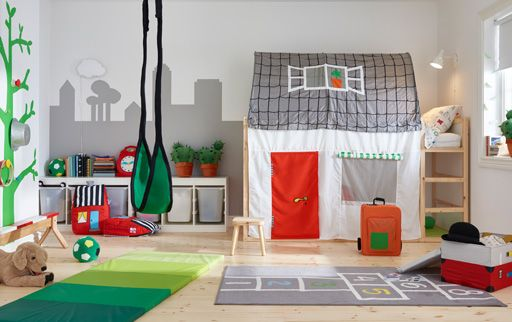 Colourful home and garden themed children's bedroom with house-shaped bed tent and outdoor games.