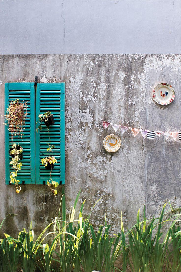 Jendela jalusi tua berwarna tosca cerah dan menjadikannya aksesori di area taman sekaligus tempat menggantung pot-pot tanaman.