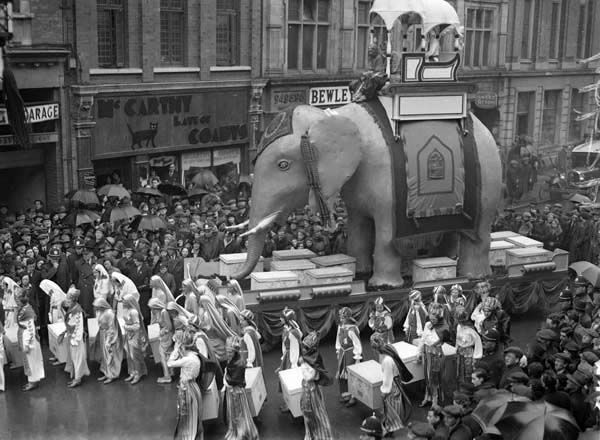https://flic.kr/p/bopCav | Lucky Elephant | Irish Hospital Sweepstakes parade through Dublin in late March 1935. Before every draw of winning tickets, there was a parade through the city, with all of the tickets carried in the boxes you can see in this photo...  Initially, couldn't work out what street this is! However, the inimitable Gerry Ward galloped to the rescue, so we now know this photo was taken on Middle Abbey Street, Dublin.  Lucky Coady's, the main (and allegedly luckiest) shop…