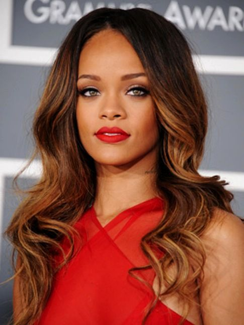 Rihanna with red lips and sexy long wavy hair.
