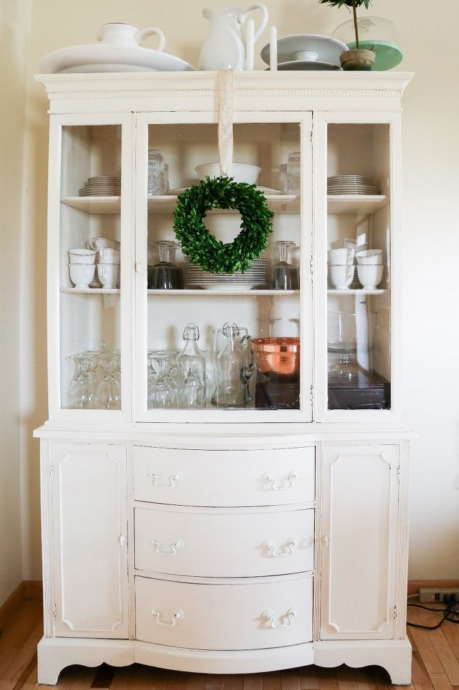 Lightly Distressed China Cabinet: A handed down china cabinet goes from a glossy cherry wood to a matte, off-white color that is lightly distressed. The final product fits in perfectly with our modern farmhouse!