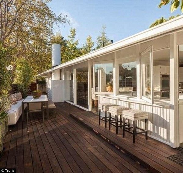 Jonah Hill's 1950s Hollywood Hills Compound: The kitchen windows open up to a unique outdoor breakfast bar, complete with upholstered stools, and a separate dining area, perfect for entertaining.