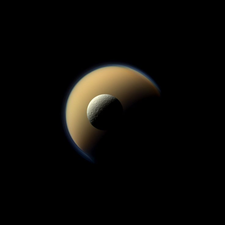 Saturn's largest and second largest moons, Titan and Rhea, appear to be stacked on top of each other in this true-color scene from NASA's Cassini spacecraft released on Dec. 23, 2013. Image credit: NASA/JPL-Caltech/Space Science Institute