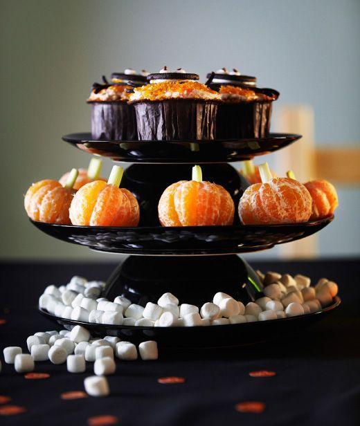 Nahaufnahme einer Servierlösung, die aus FÄRGRIK Tellern in Schwarz/Steinzeug und Schüsseln zusammengesetzt ist