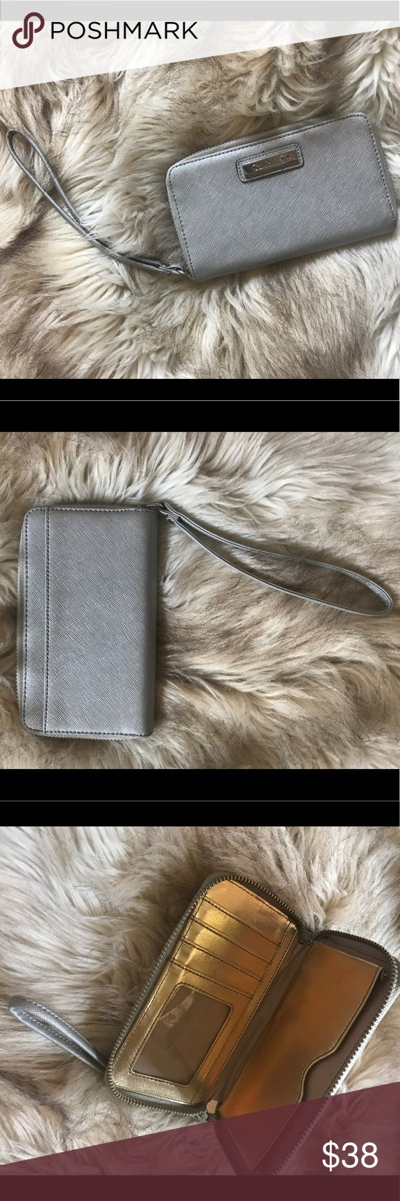 *CALVIN KLEIN* SILVER WRISTLET Silver wristlet from Calvin Klein. Gold interior with see through ID slot and 4 card slots and a cellphone pocket. Will hold phone as big as iPhone 5s. Calvin Klein Bags Wallets