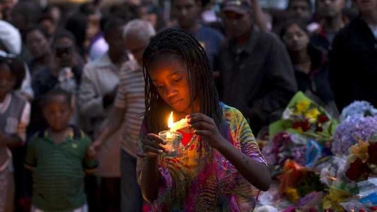 Rassemblés. Comme cette petite fille, des milliers de Sud-Africains ont déposé des gerbes de fleurs, des bougies ou des mots devant la maison de Johannesburg où a vécu Nelson Mandela. PEDRO UGARTE/AFP
