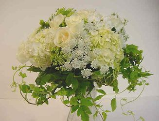 A hand-tied bridal bouquet of garden flowers - roses, hydrangea, queen anne's lace, phlox, and accented with clematis vine. Perfectly beautiful and free if you or your friends or neighbours have fresh flower gardens