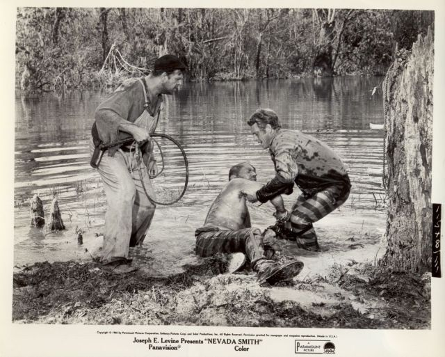 Max (McQueen) pulls Bill Bowdrie (Arthur Kennedy) from the swamp, as Big Foot (Pat Hingle) watches on.