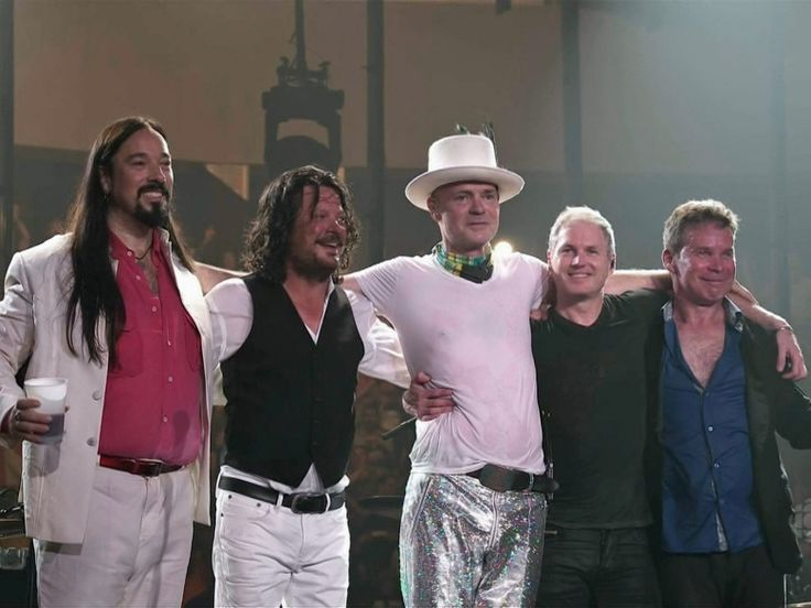 Members of The Tragically Hip gather on stage for the fans after ending their…