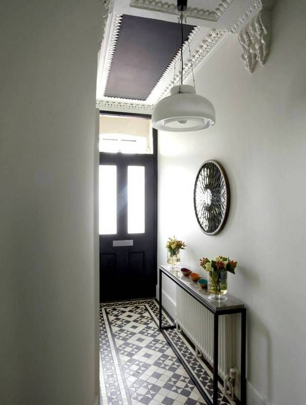 Stylish Radiator Cover Ideas For Summer | Domino. Pair the radiator in the entry with a sleek narrow console.  Black & white entry hall, foyer. Black & white floor tiles in Ohio Star quilt pattern.