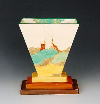 Clarice Cliff - Secrets - A shape 642 fan vase circa 1933 with rectangular stepped base rising to fan body hand painted with a stylised tree and cottage coastal landscape with green and tonal brown banding, Bizarre mark, height 16cm.