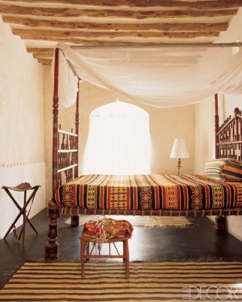 """""""In a guest bedroom in Kenya, Indian bedding and pillows made from local linens cover an antique four-poster; the stool is Egyptian, and the carpets are from Lamu."""" Would be great on a vacation."""